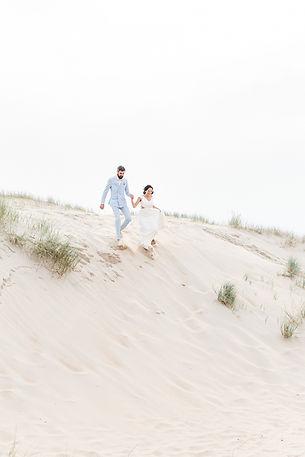 un couple marié court sur une dune de sable