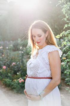 Une femme enceinte se tient debout, dans un parc. Elle porte une robe blanche et lie ses mains sous son ventre. Elle est éclairée par le soleil derrière elle. L'image est douce et lumineuse.