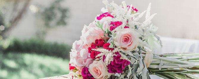 un bouquet de fleurs aux couleurs douces posé à l'horizontale. Beaucoup de vert et rose. Les tons sont pastels et l'image est lumineuse