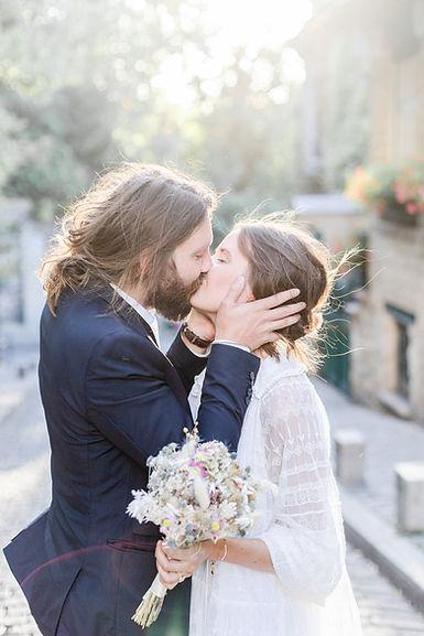 un couple de mariés s'embrasse dans une rue de Montmartre à Paris
