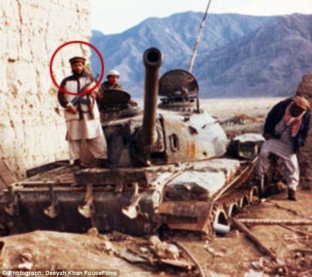 Circled, stands atop a Soviet tank holding a Kalashnikov during his time fighting jihad in Afghanistan
