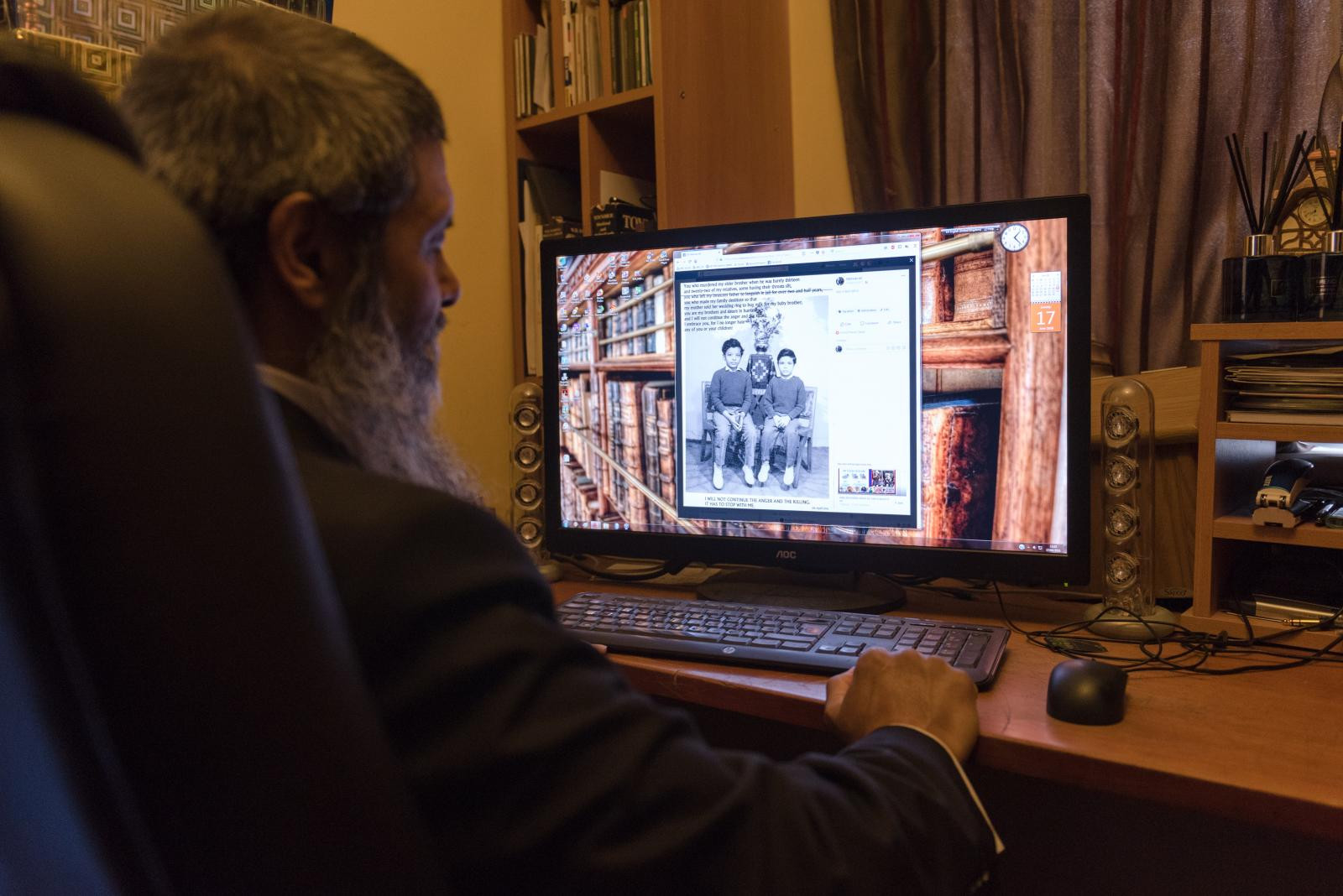 Manwar Ali in his studio looks at a picture of him and his elder brother who was killed when he was barely thirteen together with Twenty-two of his relatives died during the Bangladesh's War of Independence.