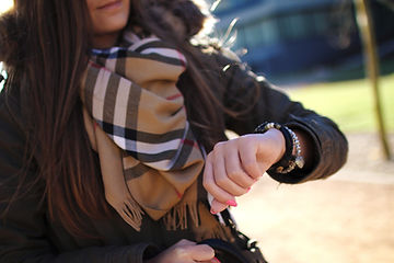 young-woman-checking-time-in-park.jpg