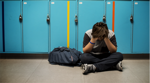 Student sitting with his head down in front of lockers because of bullying.