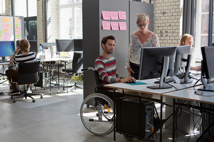 Man in wheelchair at desk with co-worker standing beside him.