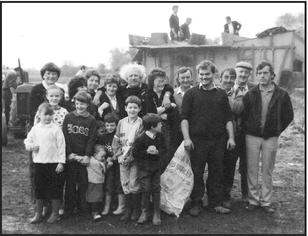 Joe Ahern (far right) with family and friends. Old threshing machine at rear.