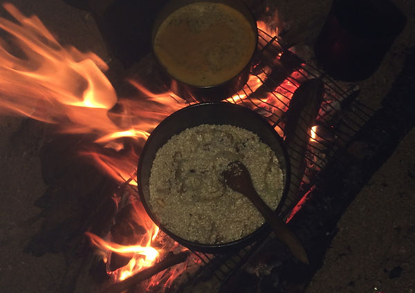 Mushroom Risotto cooking in a pot over an open fire with flames