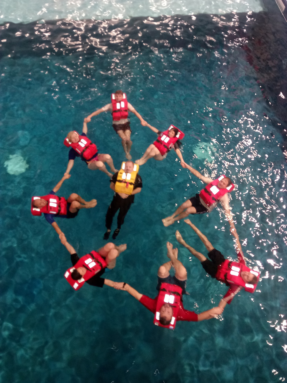 Team forming a ring of safety, in the pool.