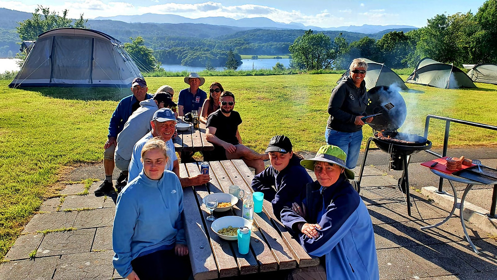 The group sat out side with the barbecue going, beautiful blue sky and the lake in the back ground with large grass area behind them.