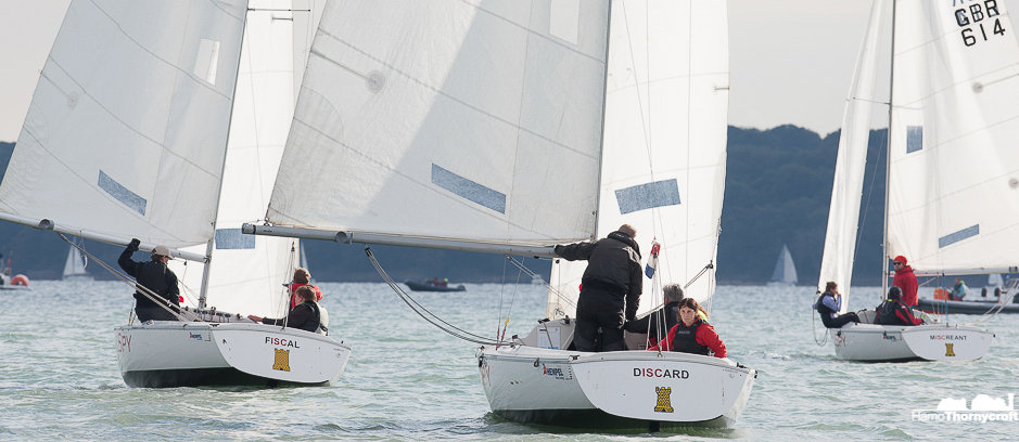 Sonars sailing down wind with two visually imparied sailors in each racing.