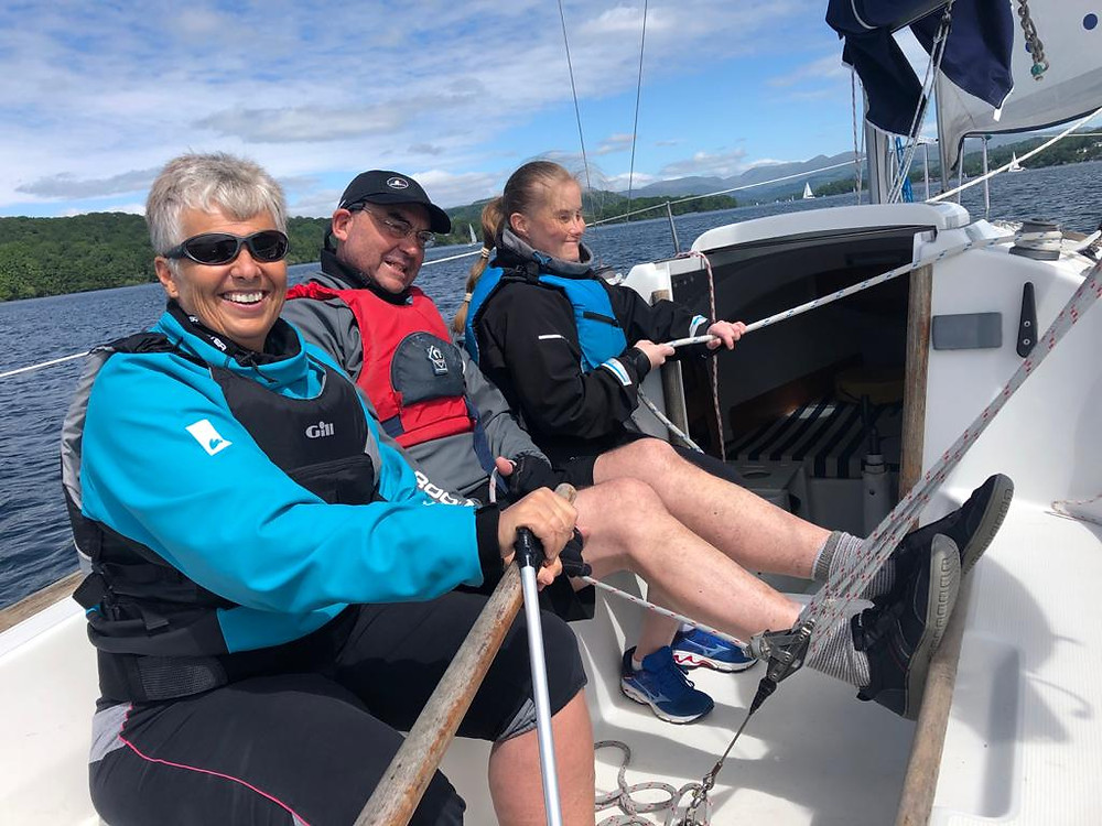 Judith on helm, Martin main and Kate on Gybe all smiles looking back at camera with the sun shinning on a 211.