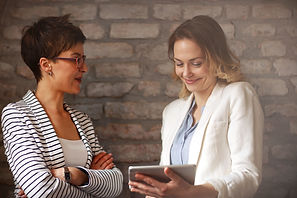 Two women looking on ipad and talk about
