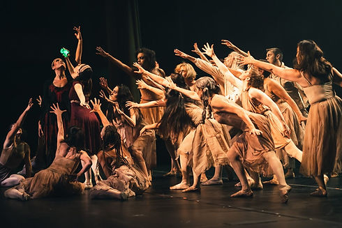 Dancers dressed as zombies reaching towards a dancer holding a green bottle