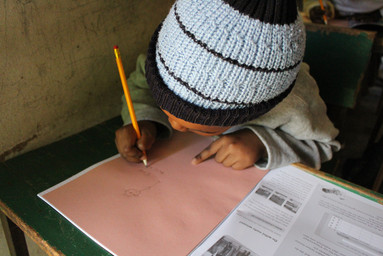 Ein Schüler der Babyschool schreibt mit seinen neuen Materialien