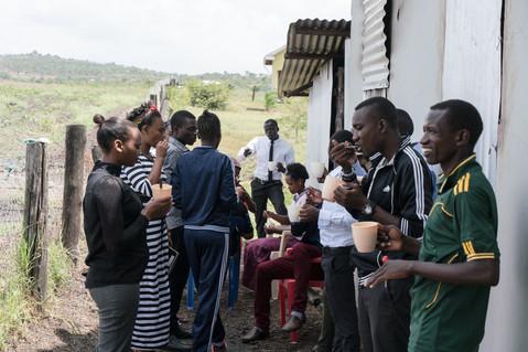 Schüler und Schülerinnen aus Tansania essen selbstgemachtes Essen
