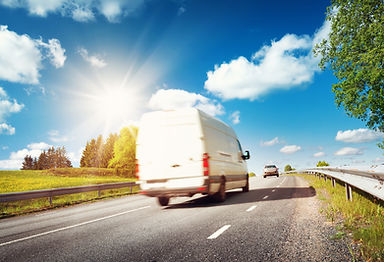 asphalt road on dandelion field with a small truck. van moving on sunny day.jpg