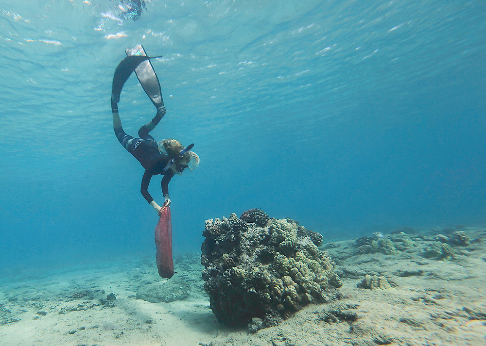 Natalie Parra searches for lead weights discarded by fishermen on the reef in Cressi.