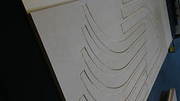 MDF is one of the best materials to cut on a CNC router table that uses vacuum suction as a means to hold down materials to be CNC cut.  This is due to it's flat even surface and porosity but also because of the density and durability that is has.  MDF's durability can be employed for a skeletal building structure or frame to support and shape other materials as in this picture.  It also offers a rigid shape that doesn't easily change unless soaked with liquids.  That makes it Ideal when an exact dimension or shape is needed as for an insert or a prototype.  It is inexpensive and can be CNC cut in various shapes and sharp or mitered edges and it comes in different colors making it good for display as well.
