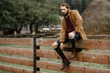 man-in-a-brown-coat-on-a-wooden-fence-UB