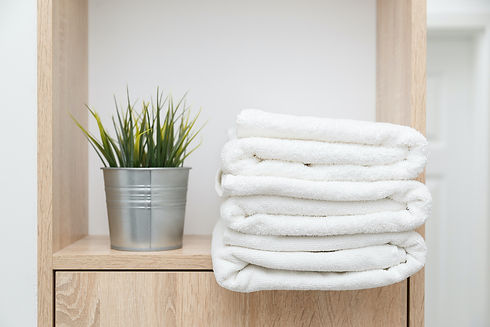 stack-of-clean-towels-on-shelf-with-gree