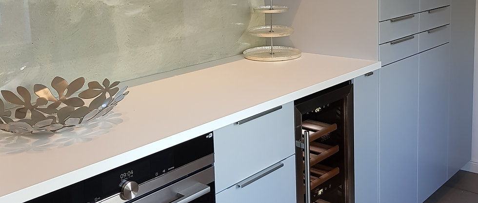 Light Grey kitchen with wine refrigerator and oven. Clouds Wallpaper and silver fruit bowl.