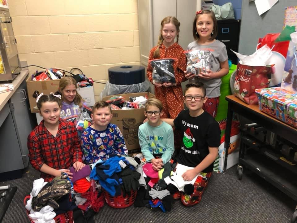 Elementary students pose with winter gear they collected for veterans and homeless.