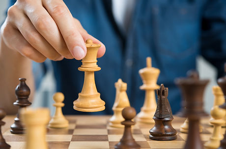 Close up of hand of man playing chess holding queen. Business man playing chess. Hand of casual busi