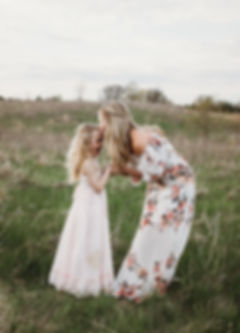 beautiful moment of mom and daughter in a grassy field by Twin Cities family photographer