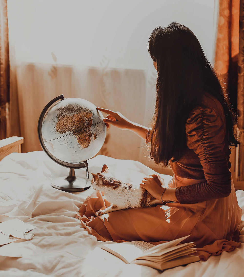 A woman looks at a globe and dreams of travel with a cat on her lap