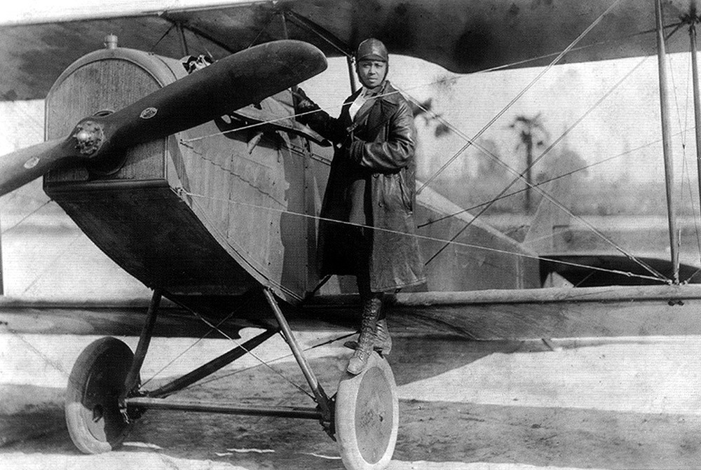 Bessie Coleman, first female African American aviator, and her plane in 1922