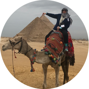 ESL teacher poses on a camel in front of pyramids in Egypt