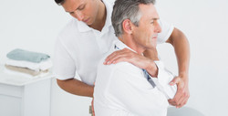 Side view of a male chiropractor examining mature man at office_edited