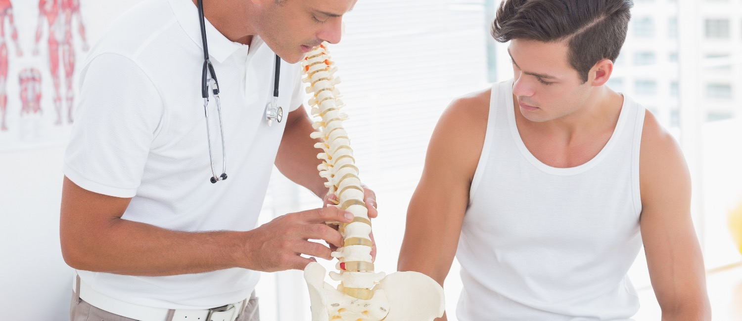 Doctor showing anatomical spine to his patient in medical office_edited