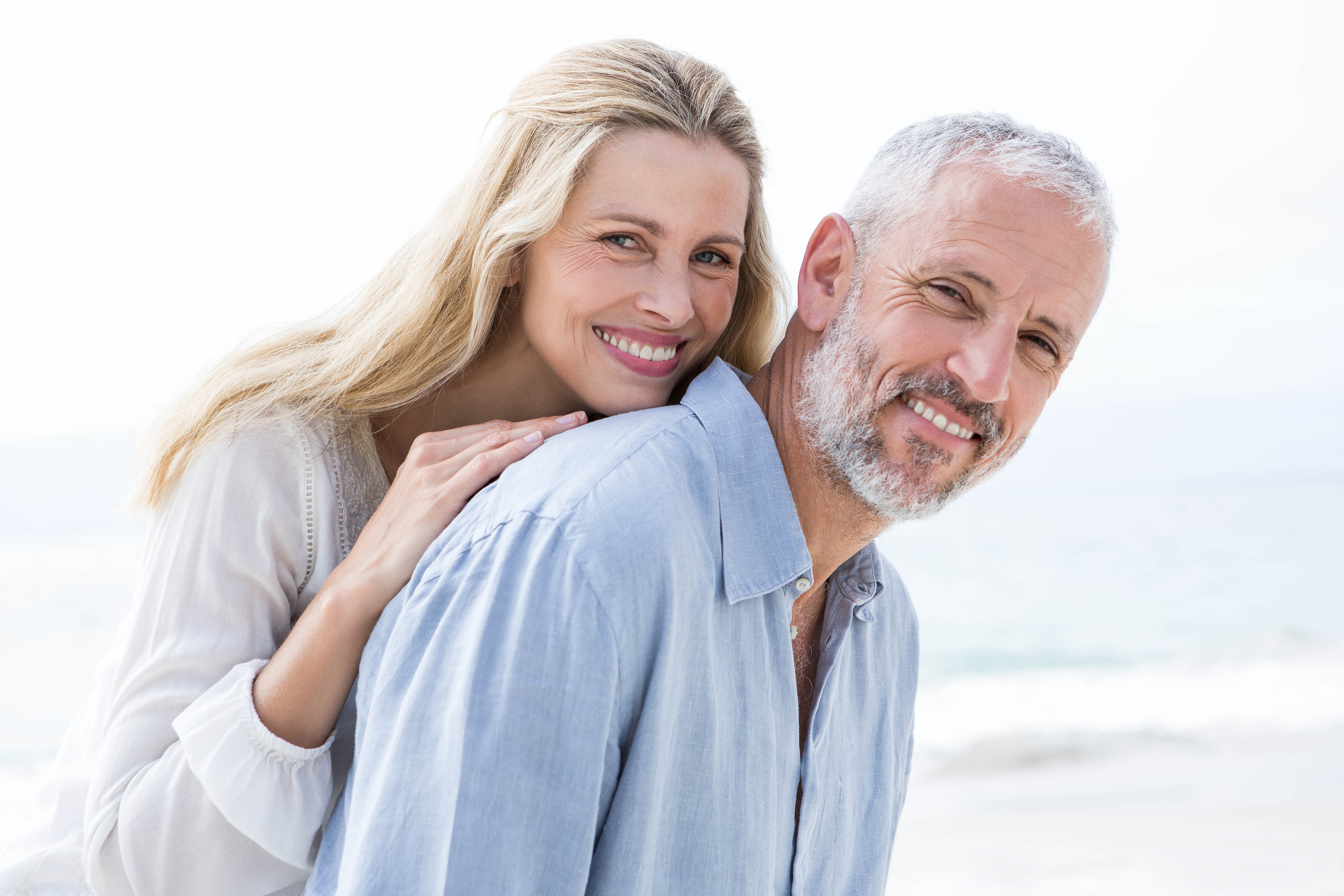 Happy couple hugging each other and smiling at camera at the beach