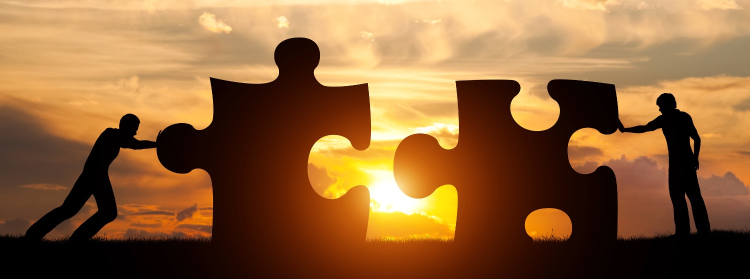 Two men connect two puzzle pieces. Sunset sky. Concept of business solution, teamwork, solving a pro