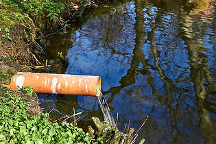 Pipe discharging wastewater into river.j