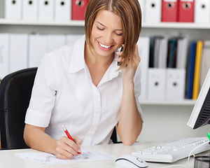 Woman at desk on the phone, smiling and writing down notes