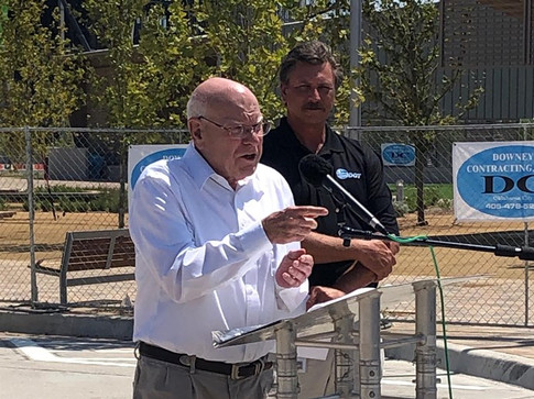 TRUST board member Gary Ridley makes a point to the audience at the Oklahoma City Boulevard grand opening as Secretary of Transportation and ODOT executive director Tim Gatz listens.
