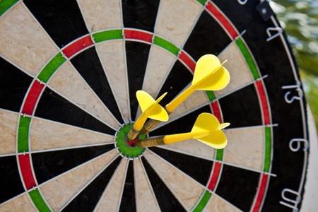 Dart board with 3 darts in bullseye