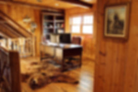 Grand Wisconsin log home loft office with carved wood desk