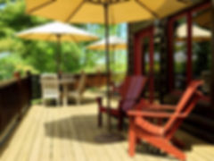 Lake home sun porch teak furniture with sun umbrellas