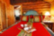 Vintage Wisconsin full log cabin master bedroom painted bed frame