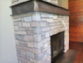 Steel wrap mantel over rock mason fireplace with steel inset hearthstone