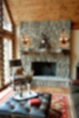 Stone fireplace with timber mantel and mica double light sconces