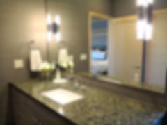 Floating bathroom sconces in large wall to wall master bath mirror