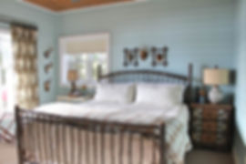 Painted shiplap wood wall guest bedroom with hickory frame bed