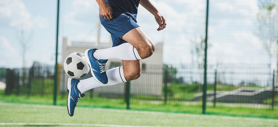 cropped-shot-of-soccer-player-jumping-with-ball-on-C5SPBQD_edited.jpg
