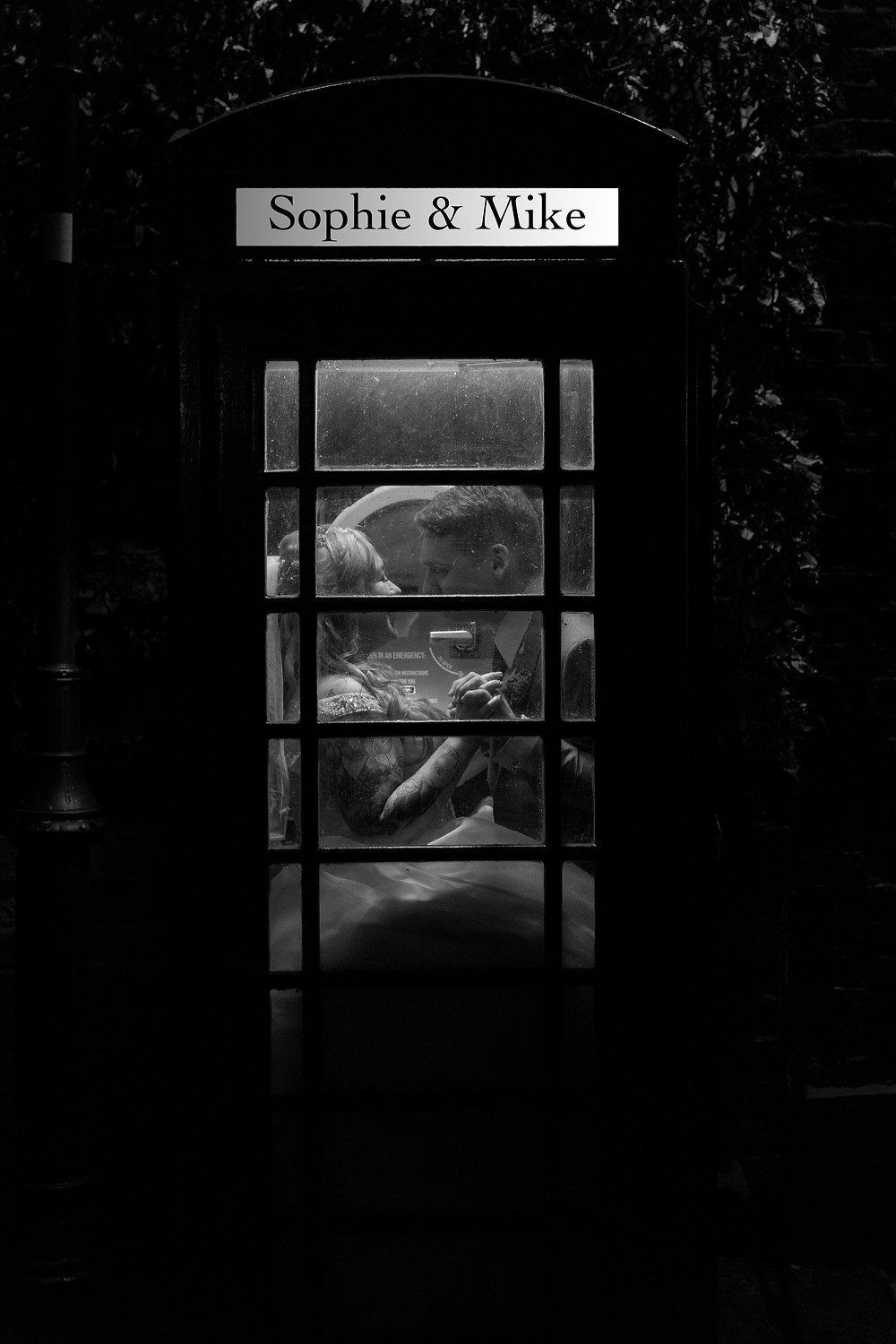 Bride and groom in a telephone box.