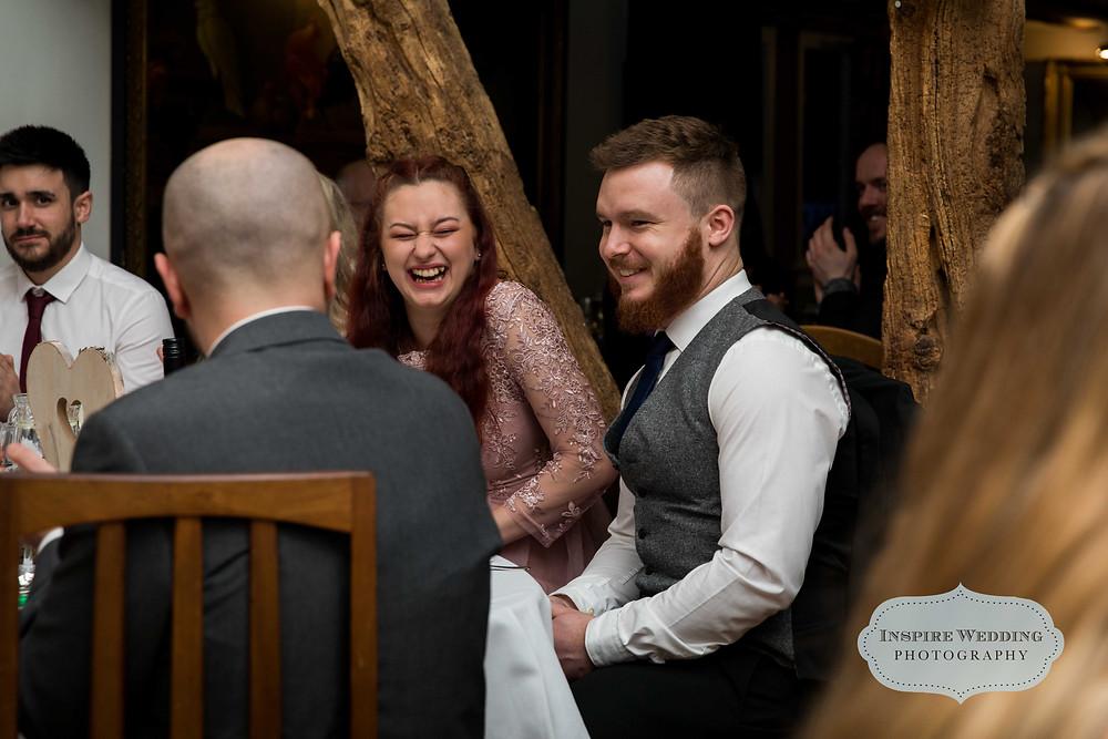 Bridesmaid laughing during best man speech