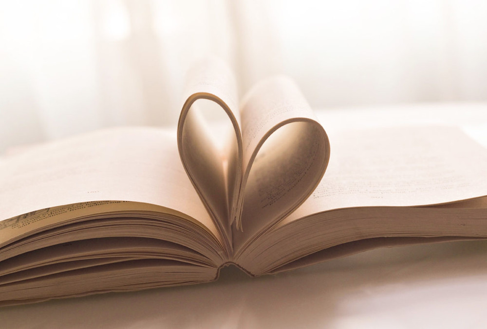 Books with papers formed like a heart